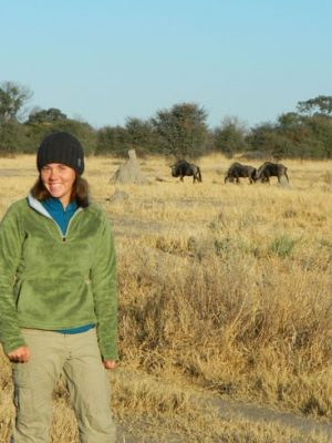 Lindsey Rich on the savannah with wildebeest in the background