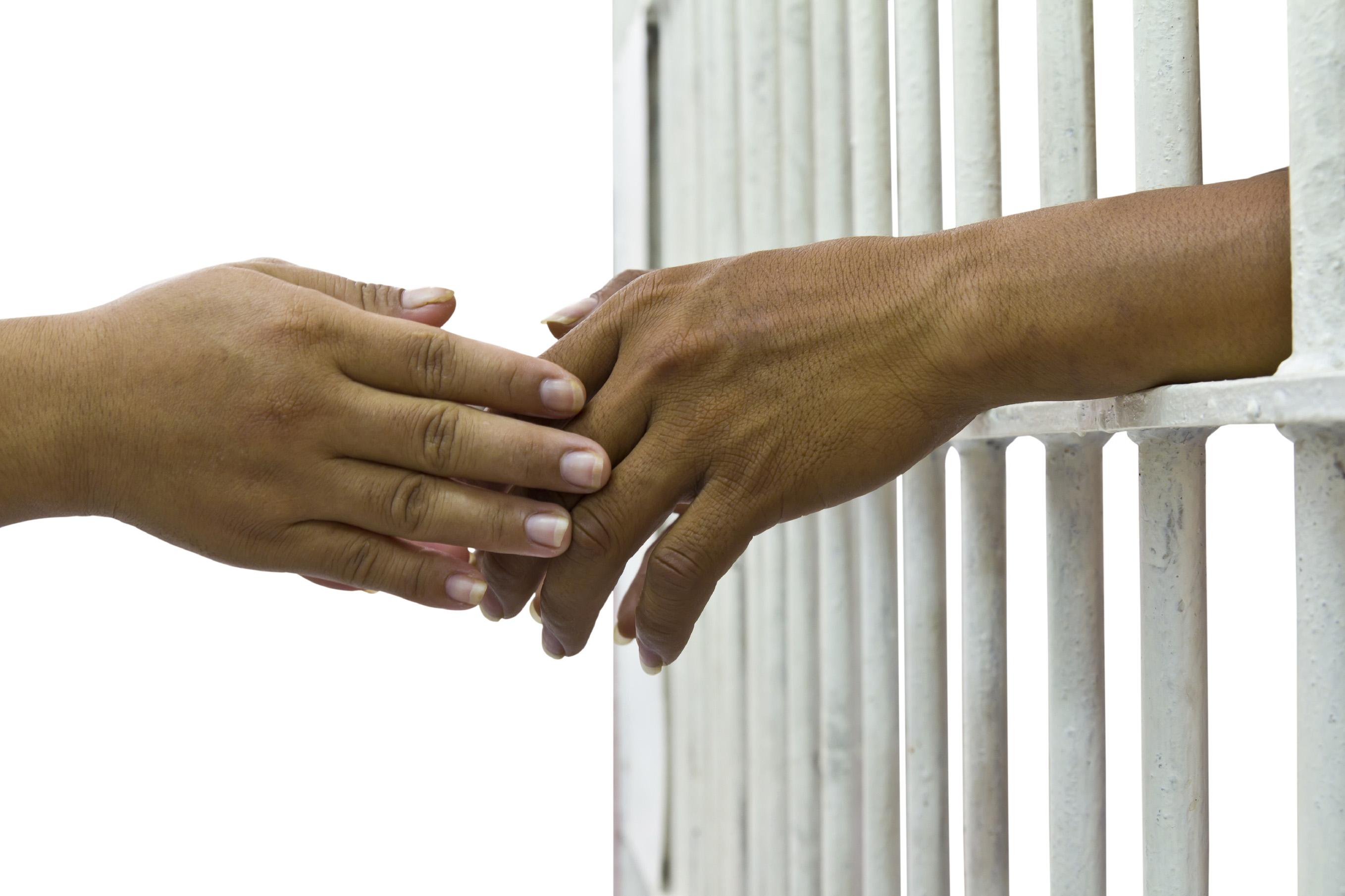 Two hands reach for one another through the bars of a prison cell.