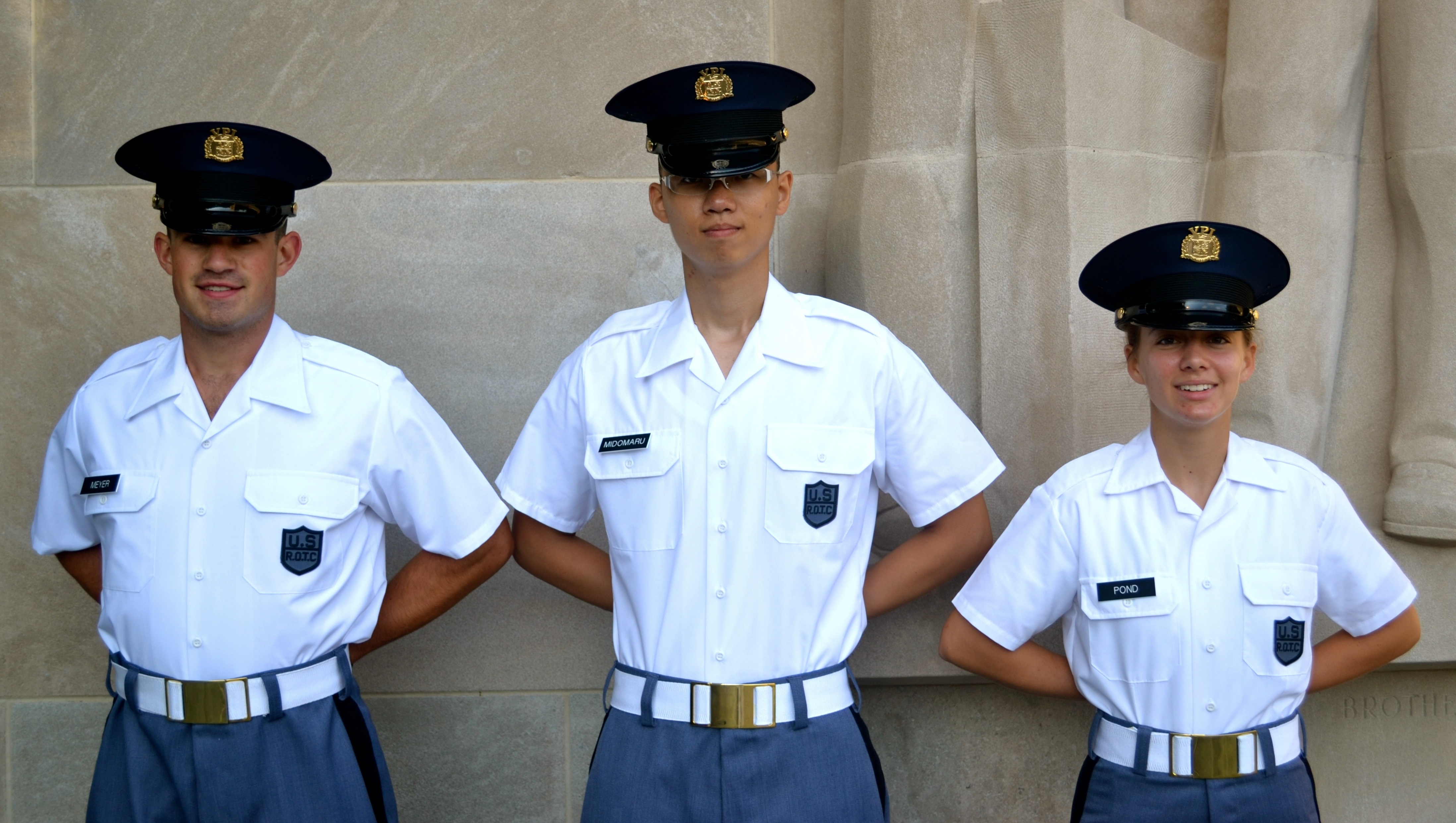 From left to right are Cadets Thomas Meyer, Ronald Midomaru, and Joelle Pond standing in front of the Brotherhood Pylon.