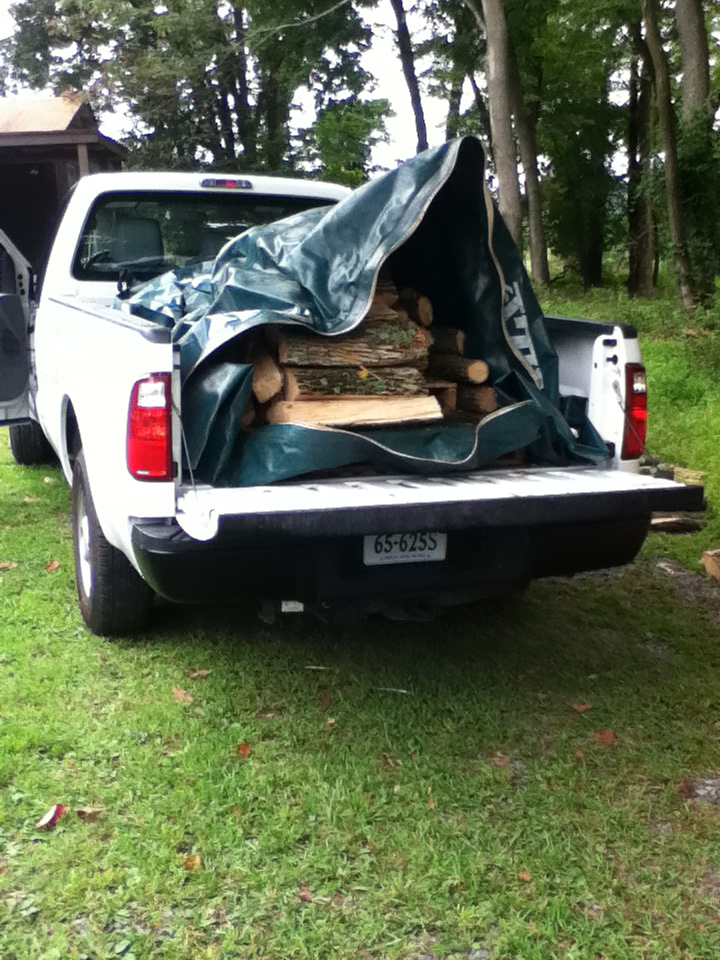 A load of firewood in large plastic bag in the bed of a pickup truck.