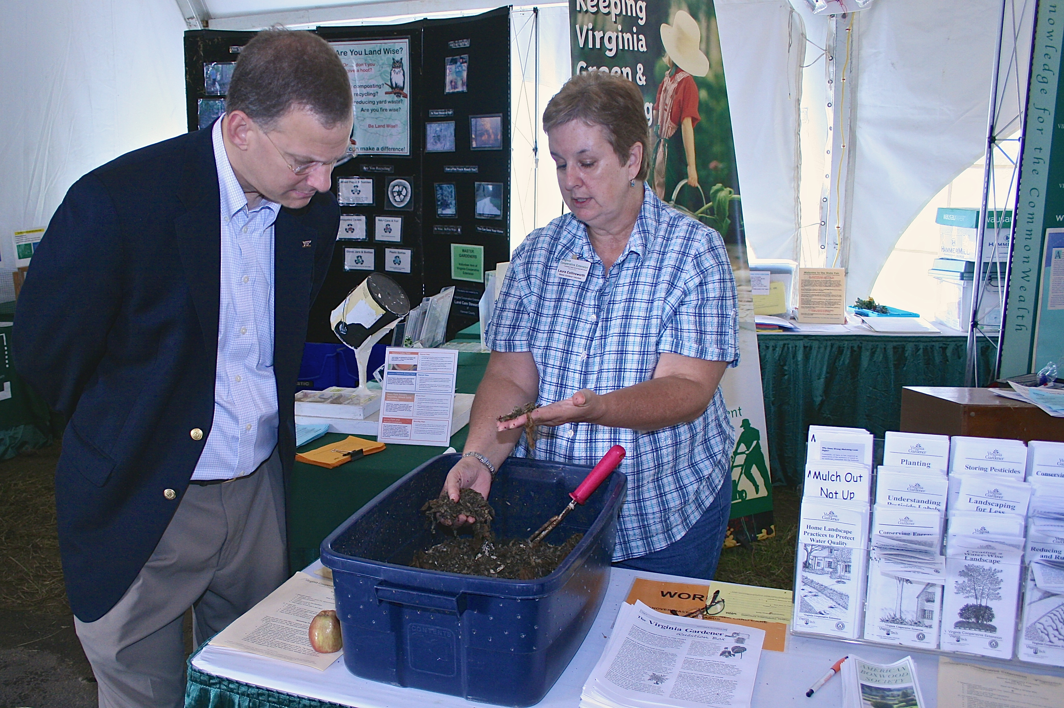 A Master Gardener shows a fairgoer a tray of compost.