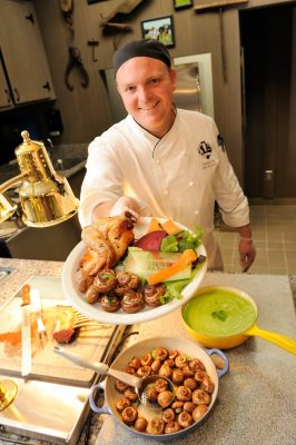 Chef displays plate of locally grown food.