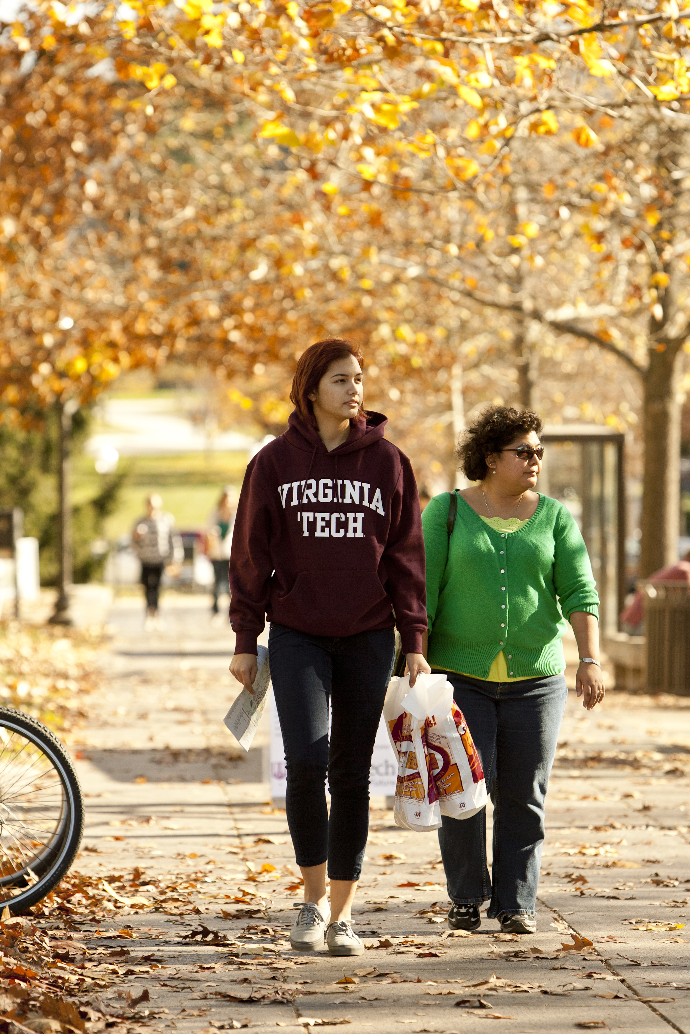 Student and mother walking under autumn leaves.