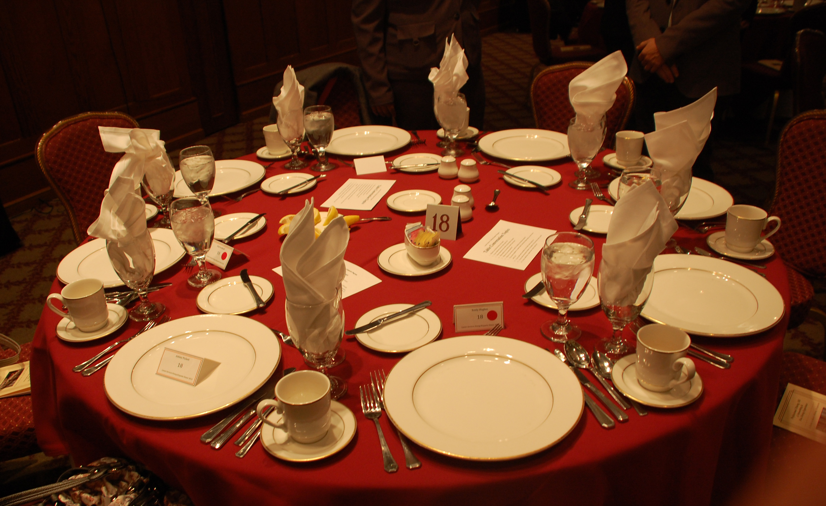 A formal dinner setting on a red tablecloth