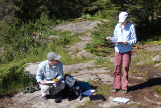 Campsites with bedrock on the sloped areas from the landing are more resilient. Here, doctoral students Jeff Feldhaus (left) and Holly Eagleston take measurements.