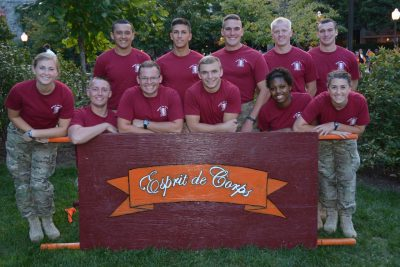 Team image of Esprit de Corps posing with the push-up board, wearing army pants and maroon shirts