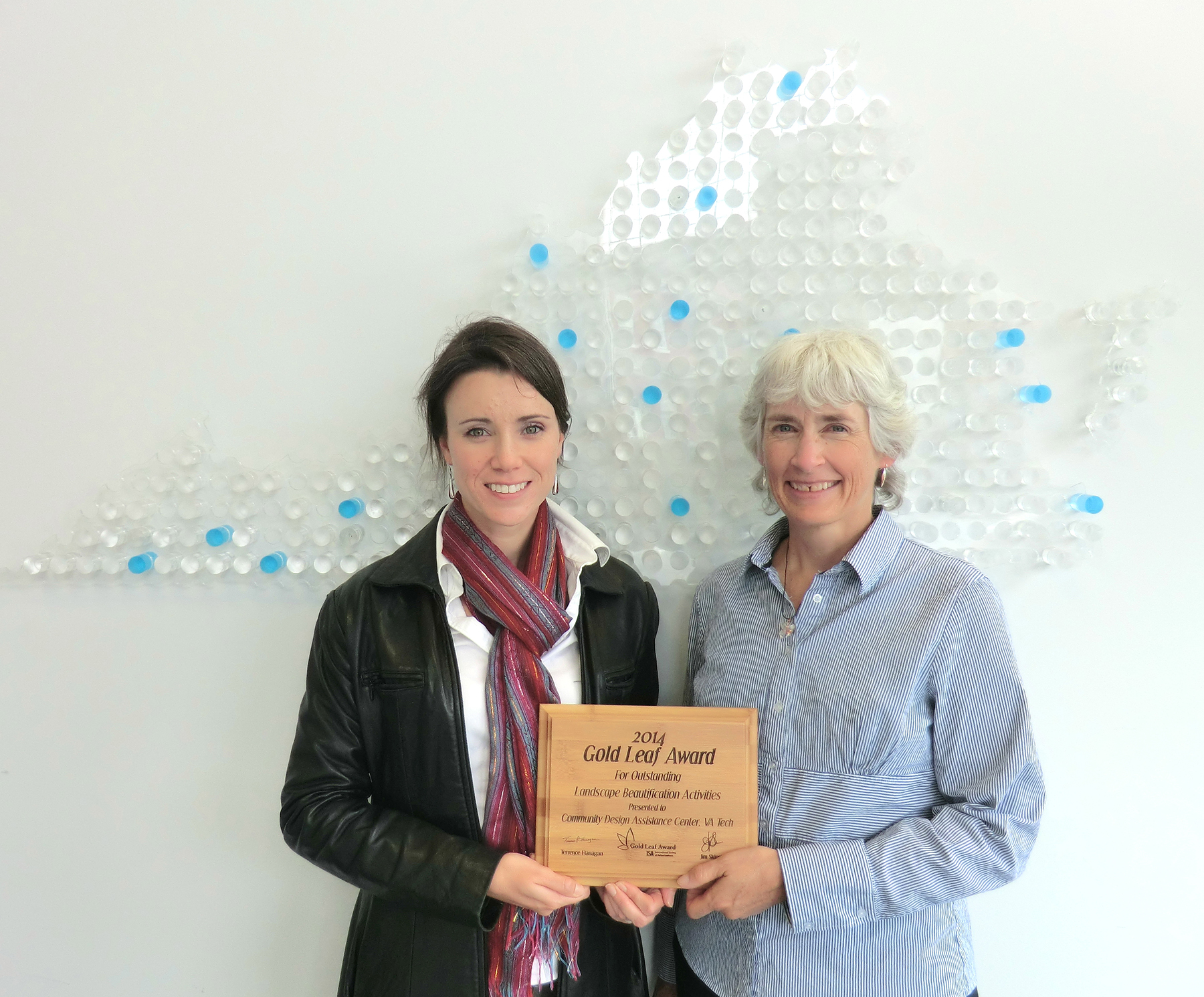 Lara Browning and Elizabeth Gilboy hold the wooden plaque they received for the Gold Leaf Award.