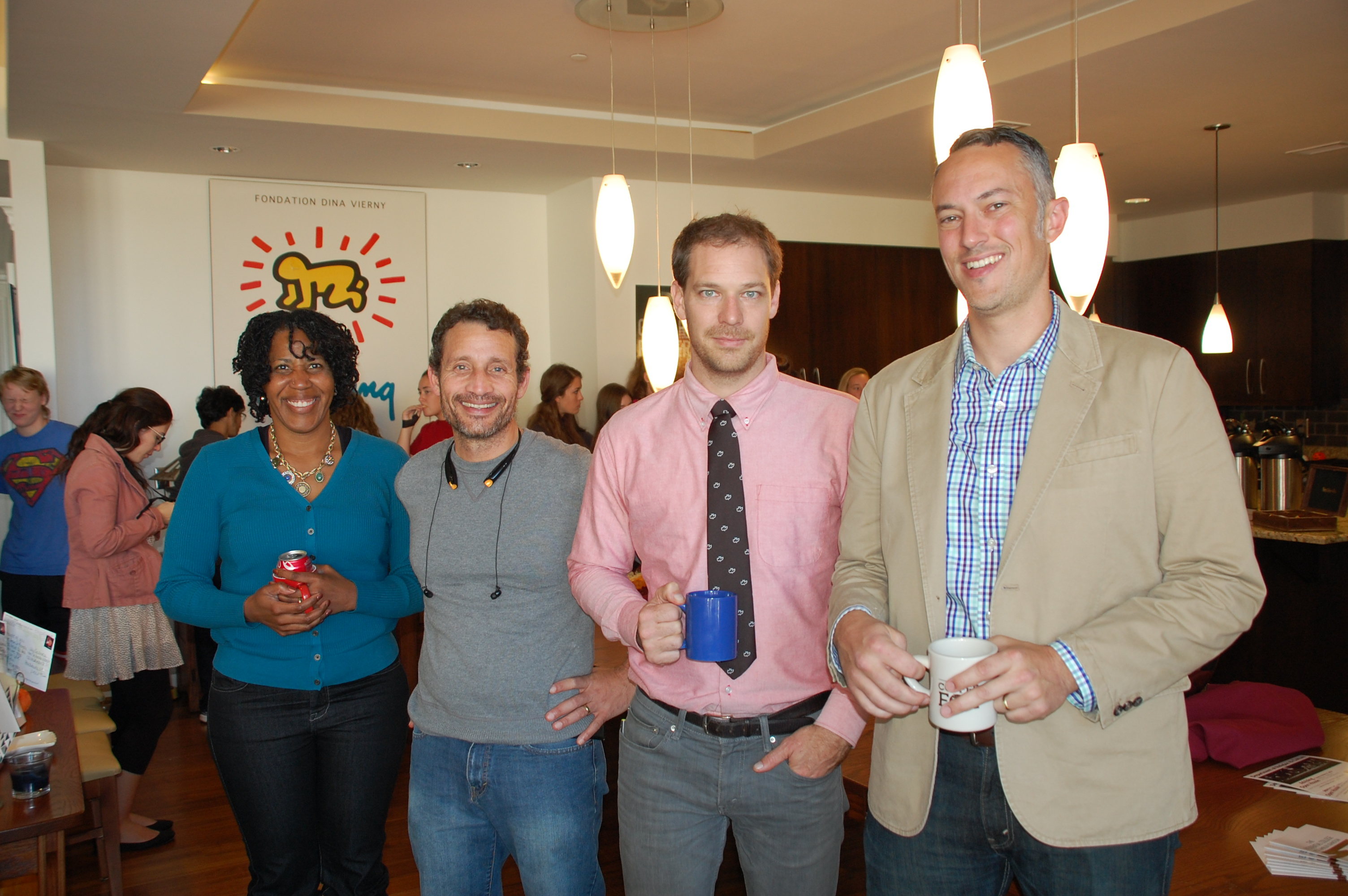 Four faculty principals from West Ambler Johnston pose for a picture in an apartment during a residential college event.