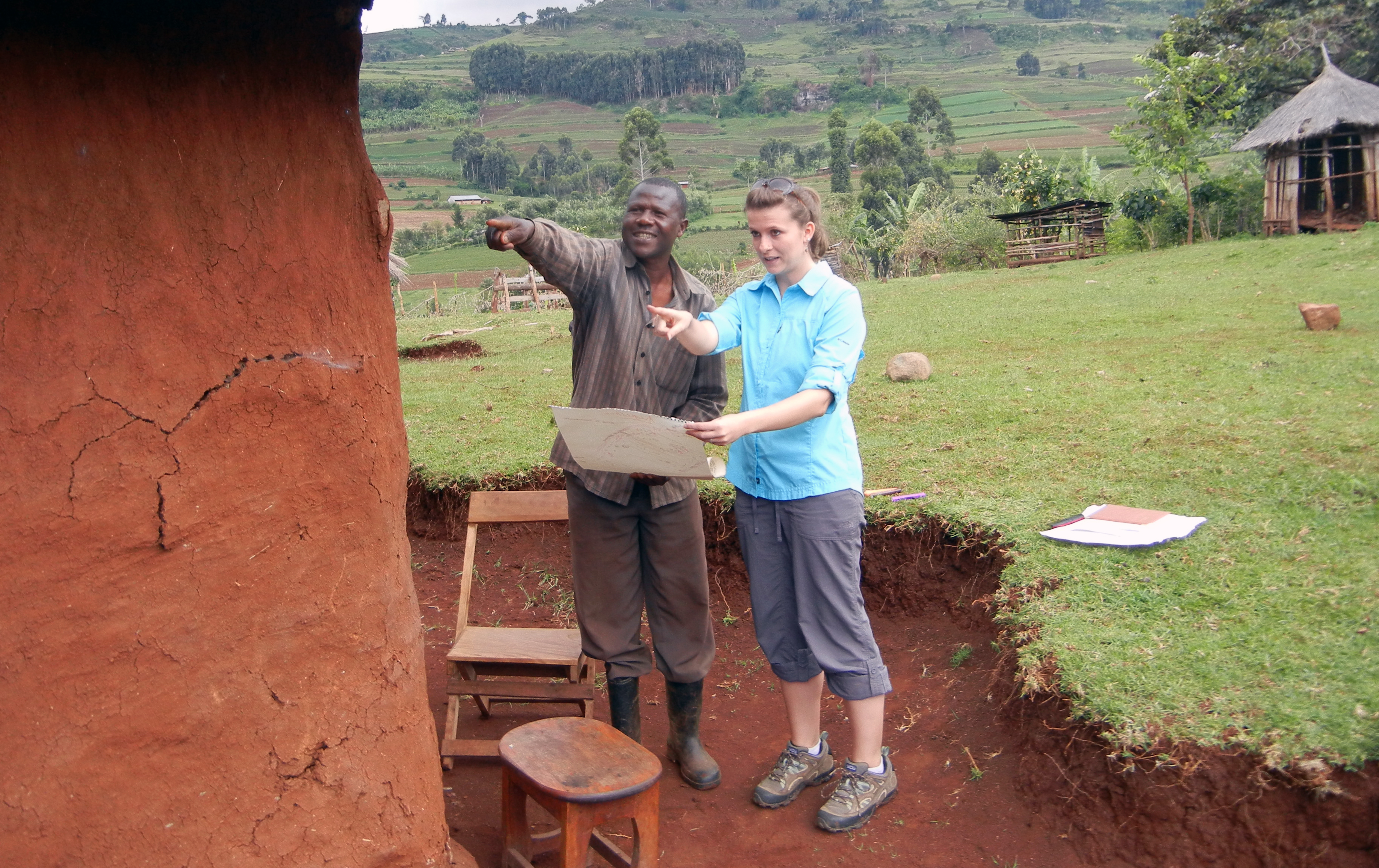 A Virginia Tech employee stands next to a farmer with a map in Uganda.