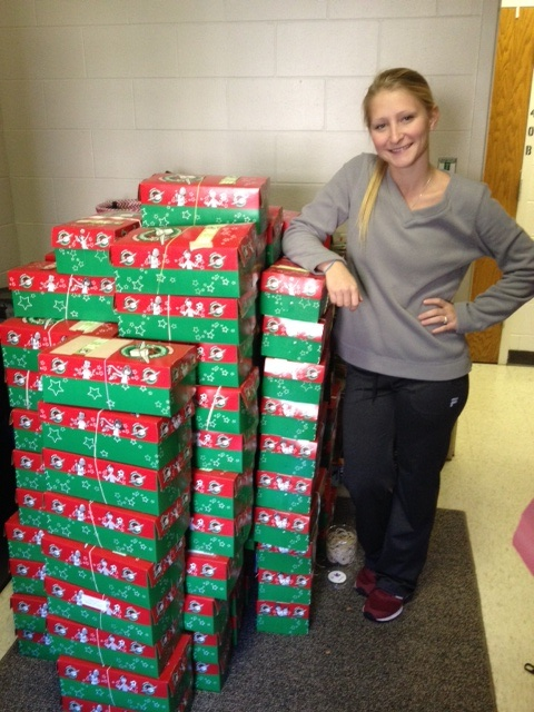 Student with shoeboxes collected, filled, and sent to children in need.