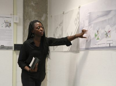 A young woman presents a design board to an audience.