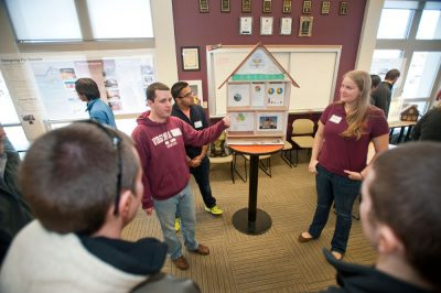 Three Virginia Tech students stand on either side of a small model house while other students look on.