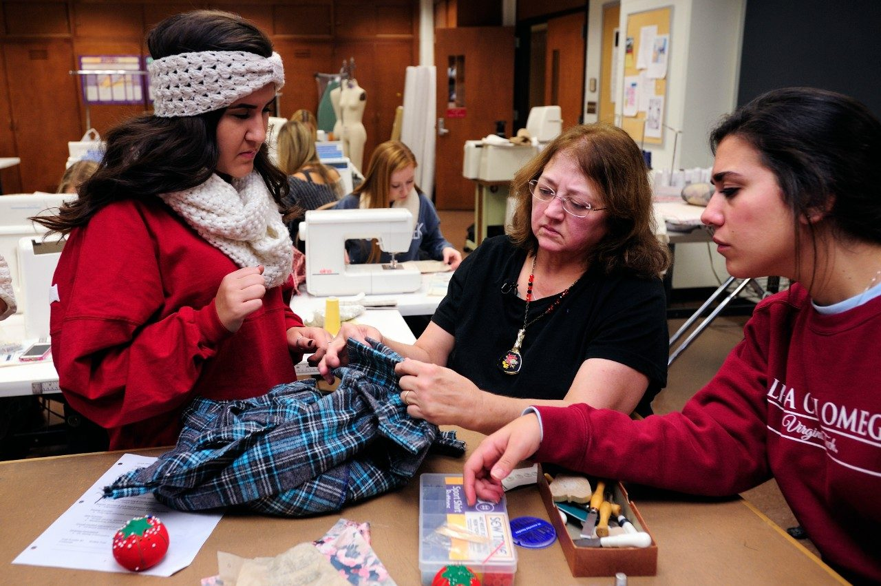 Peggy Quesenberry, center, works with students in an apparel production class.