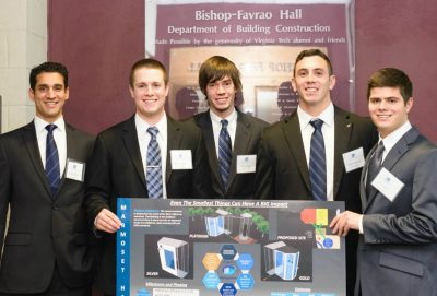 The five students on the third place team stand with their presentation board.