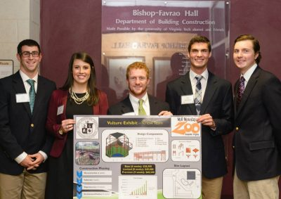 The five students on the team that tied for third place stand with their presentation board.