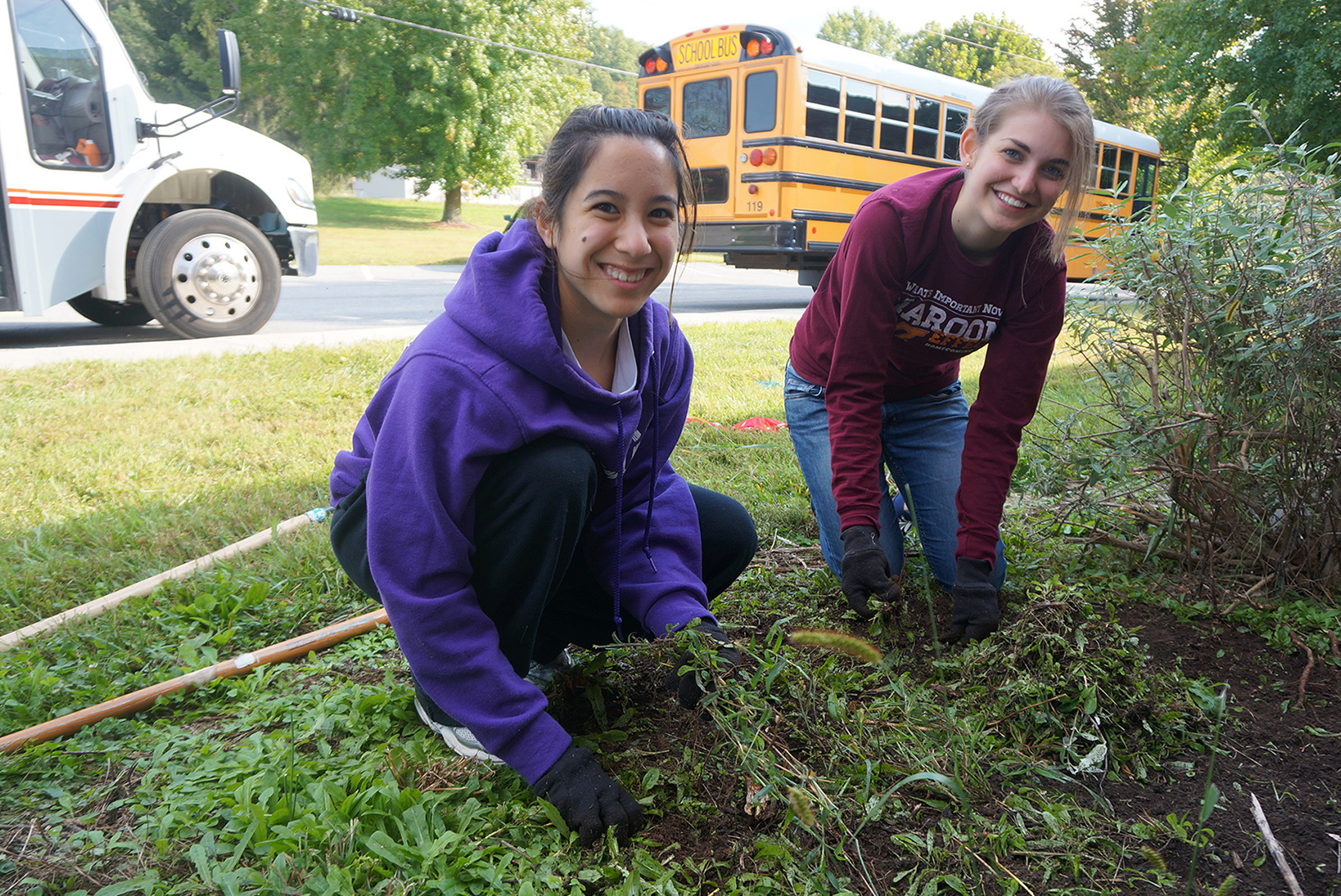 Two students perform landscaping at an elementary school