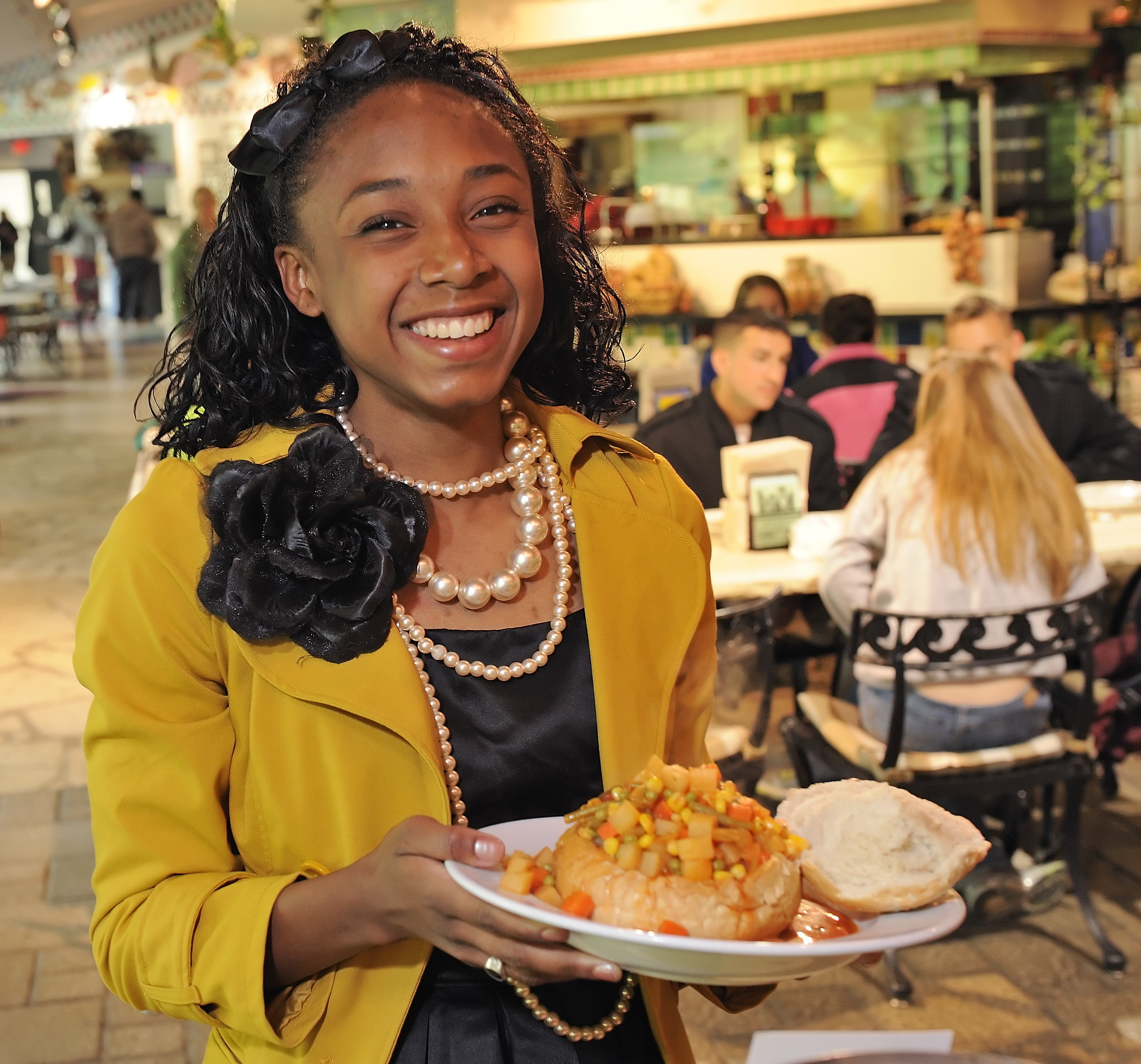 A student smiles as she displays a bowl of vegetable soup at West End Market.