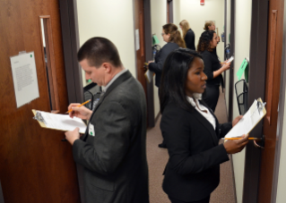 Prospective students rotate through interview rooms where an interviewer evaluates their response to a scenario dealing with topics such as communication, decision making, and diversity.