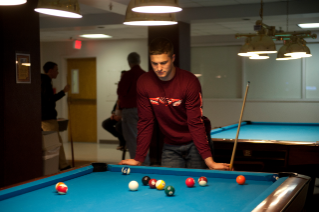 A student concentrates on his next move during a game of billiards in BreakZONE, Virginia Tech's home of billiards, bowling, table tennis, and EndZONE.