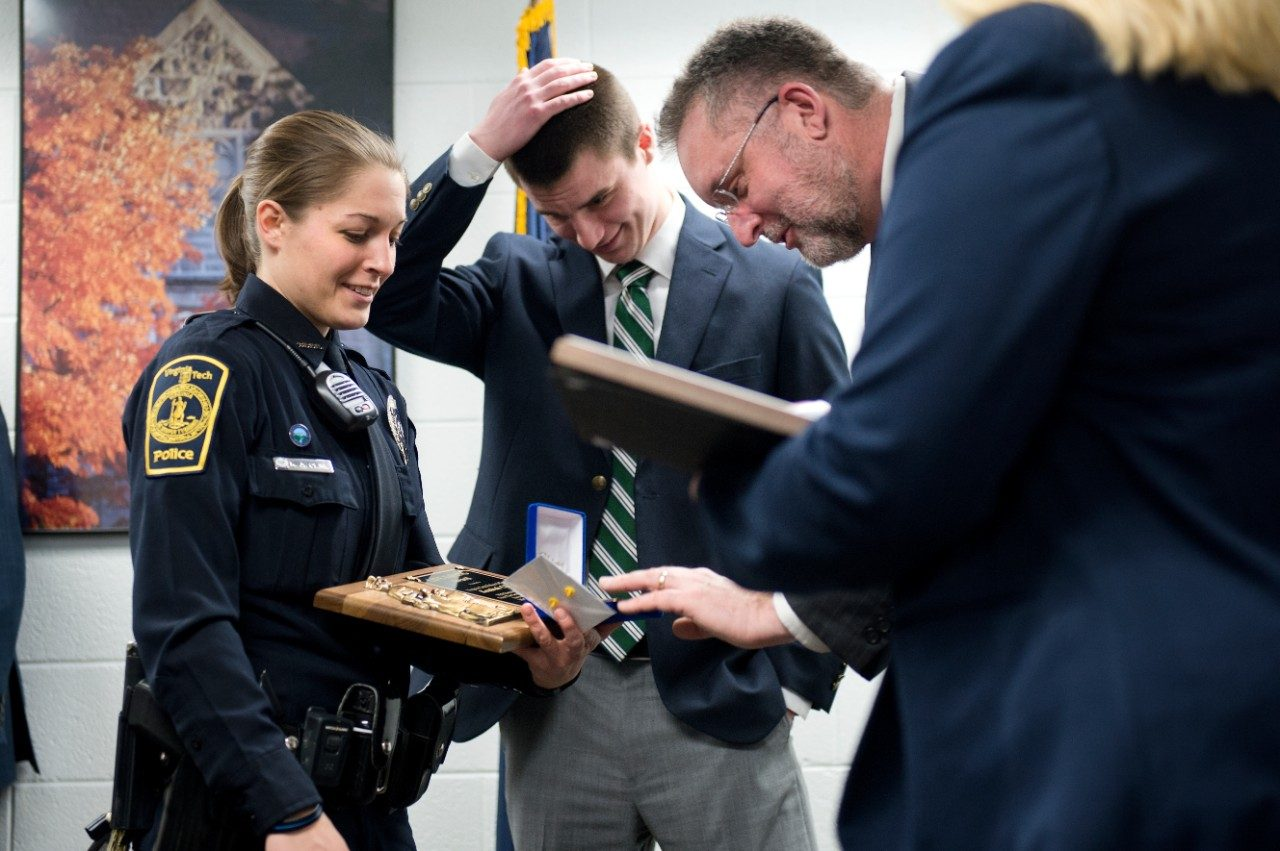Virginia Tech police officer Kendrah Cline with Virginia Tech student Michael Senoyuit IV and his father Michael Senoyuit III (reading plaque). Cline received the police department's lifesaving medal for saving the life of the younger Senoyuit on campus last fall.