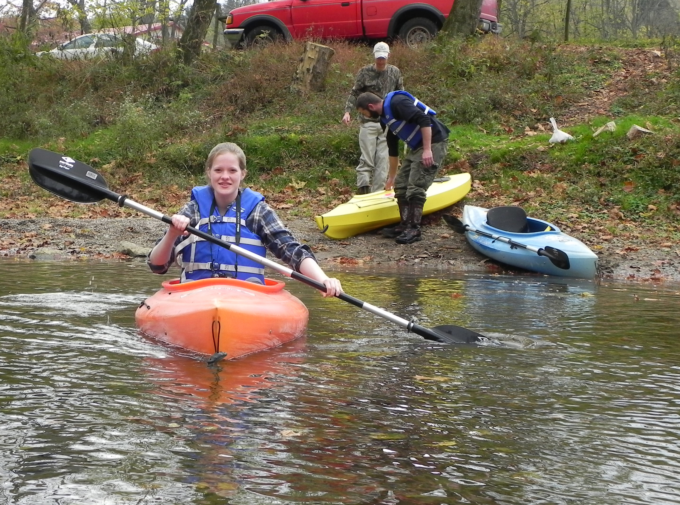 Student in kayak with other students on riverbank