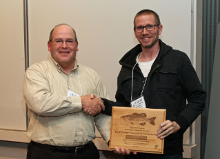 Alumnus John Copeland, left, a fisheries biologist with the Virginia Department of Game and Inland Fisheries, presents alumnus Brian Watson, the agency's aquatic invertebrate project leader, with the Virginia Chapter of the American Fisheries Society's Eugene W. Surber Professional Fisheries Scientist Award. Copeland, past chapter president, is a past recipient of the award.