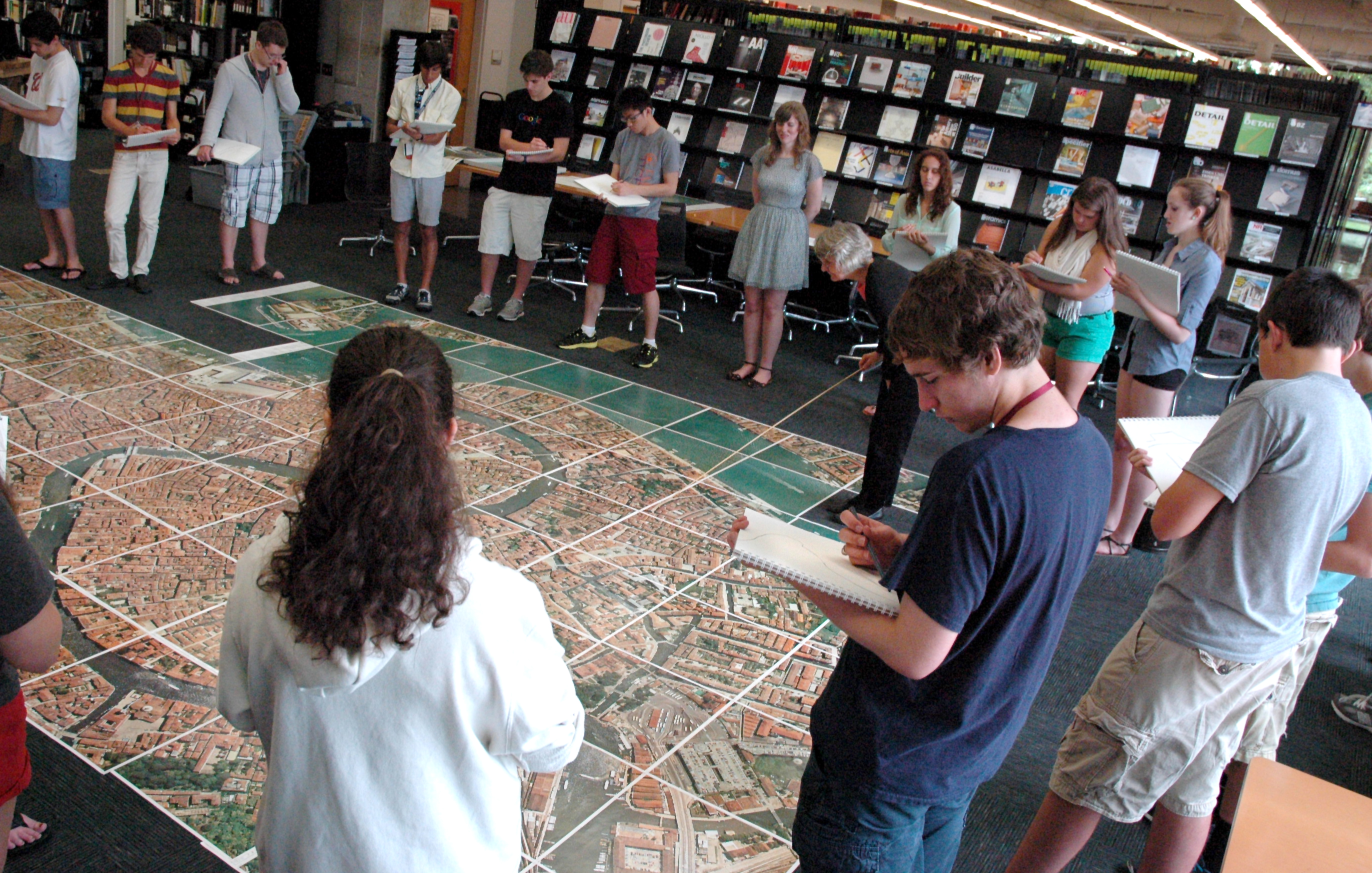Students with sketchbooks gather around a large map on the floor.