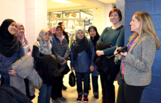 Claire Peters (right), assistant principal at Washington-Lee High School in Arlington, Virginia, gives a tour to Virginia Tech Language and Culture Institute instructor Christine Bobal (second from right) and a group of visiting high school teachers from Malaysia.