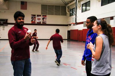 A team member explains the basics of cricket to Virginia Tech students in War Memorial Gym.