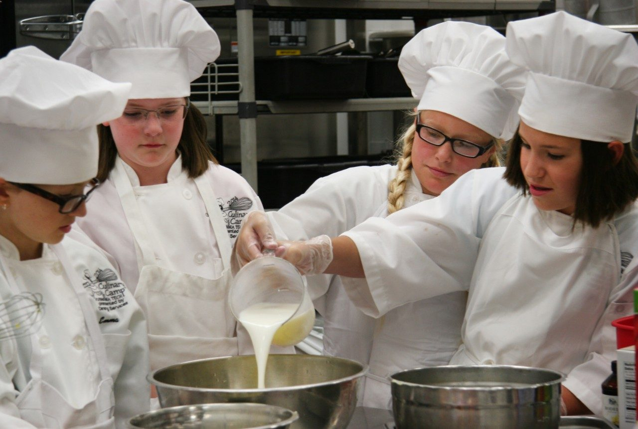 Campers from the 2014 Basic Culinary Camp work together to make batter for French toast.