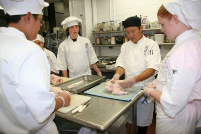 Chef and Culinary Camp students work with a whole chicken