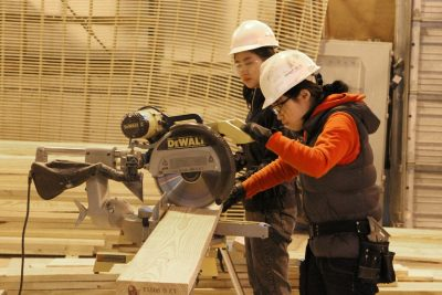 Two students cutting a board with a circular saw.