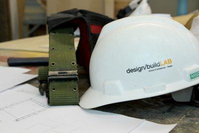 A helmet and toolbelt sit on top of building plans.