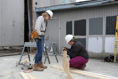 Two female college students in hard hats mark wood to cut.