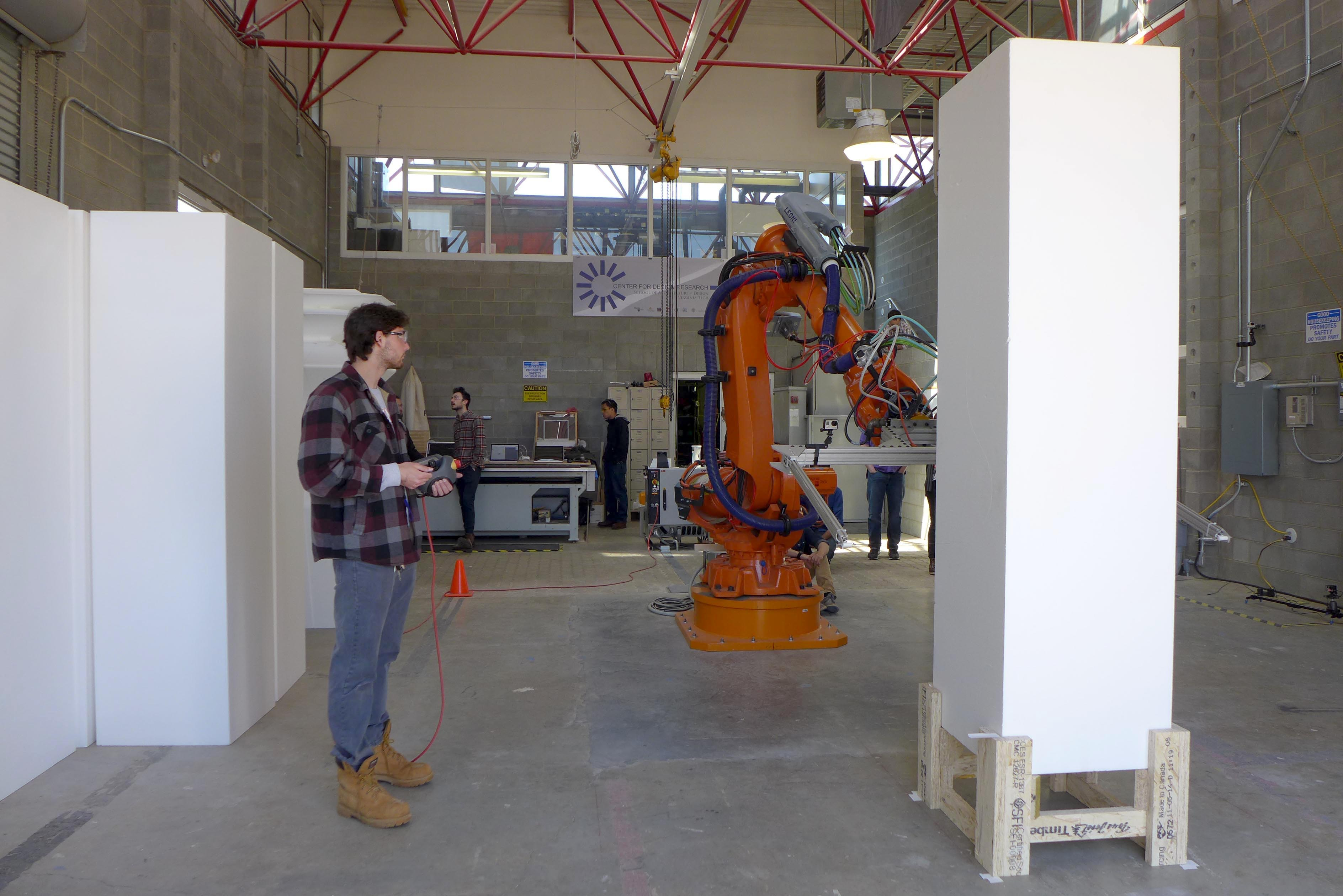 A young man controls a large industrial robot with a remote control as it prepares to cut a 7-foot styrofoam block.