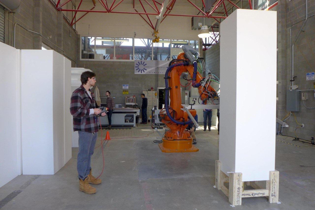 A summit participant works with the large robot in the Design Robotics Studio.