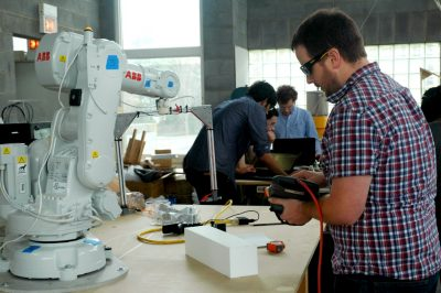 A summit participant works with a robot to create a small prototype.