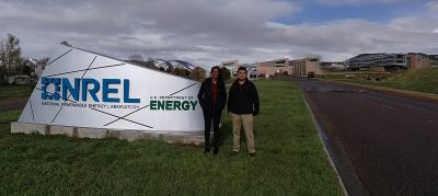 Two students stand in front of a sign with a large laboratory complex in the background.