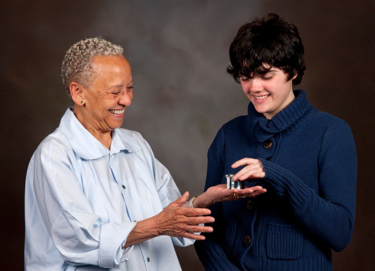 Nikki Giovanni presents Gretchen Goeke Dee a hand-crafted statue, plus $1,100, for the first place prize in The Steger Poetry contest.
