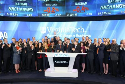 As President Sands and fellow Hokies look on, Dean Sumichrast presses the button to mark the start of the day's trading at Nasdaq. © 2015, The NASDAQ OMX Group, Inc.