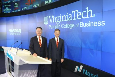 President Timothy Sands and Dean Robert Sumichrast pose at Nasdaq MarketSite's broadcasting studio.