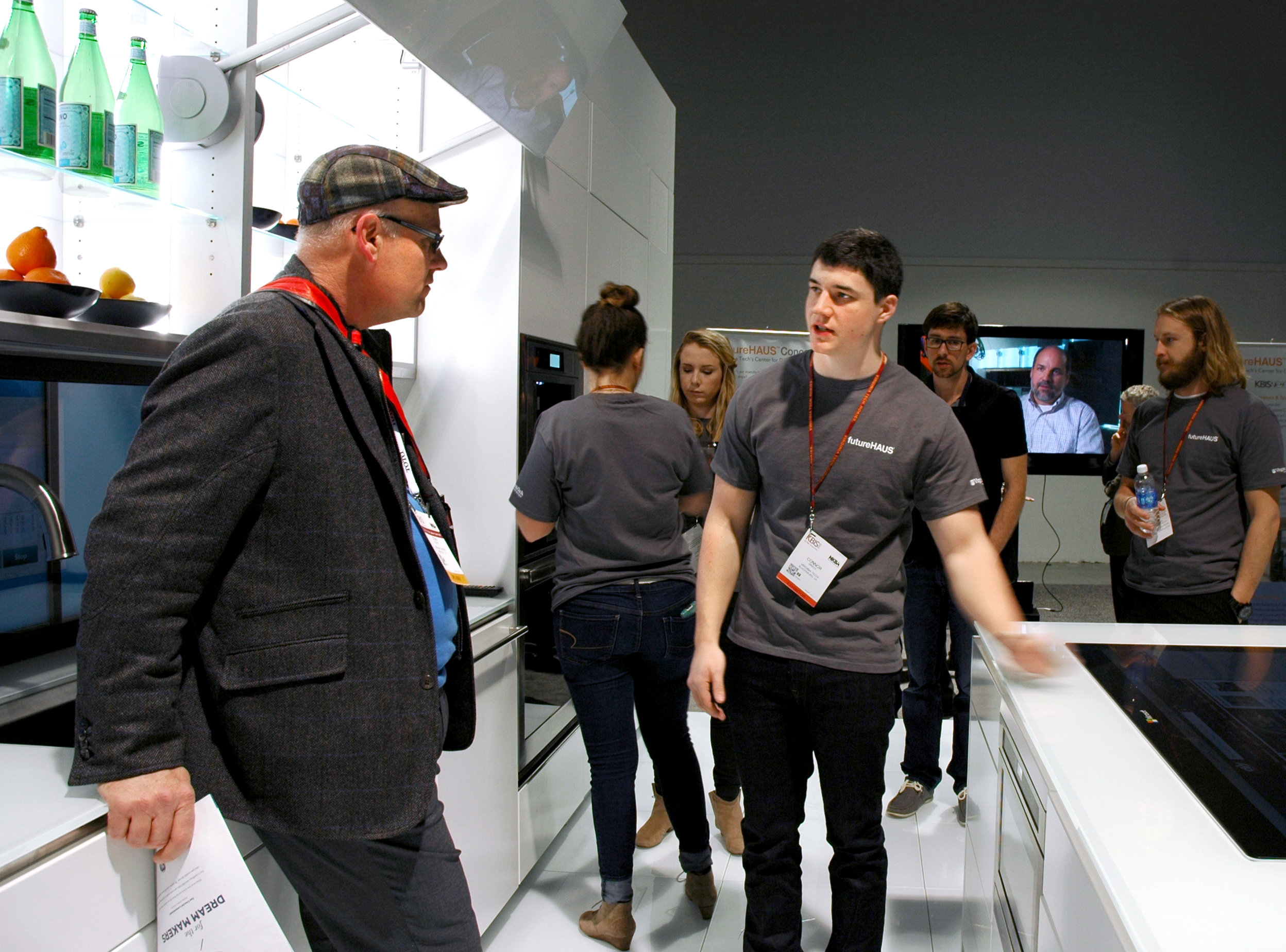 A man stands in the kitchen listening to a college student as he explains a touch screen surface embedded in a kitchen island.