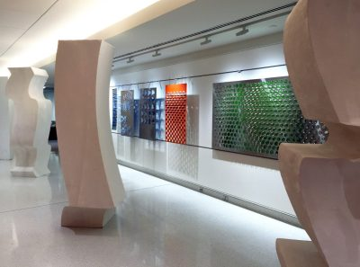 Large column sculptures in the foreground with colorful metal screens hung along a wall.