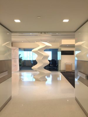 A six-foot white undulating column on display in the hallway of an office building.