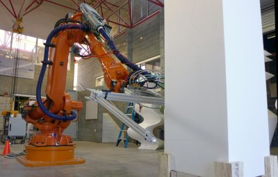 A large orange industrial robot slices through a white tower.