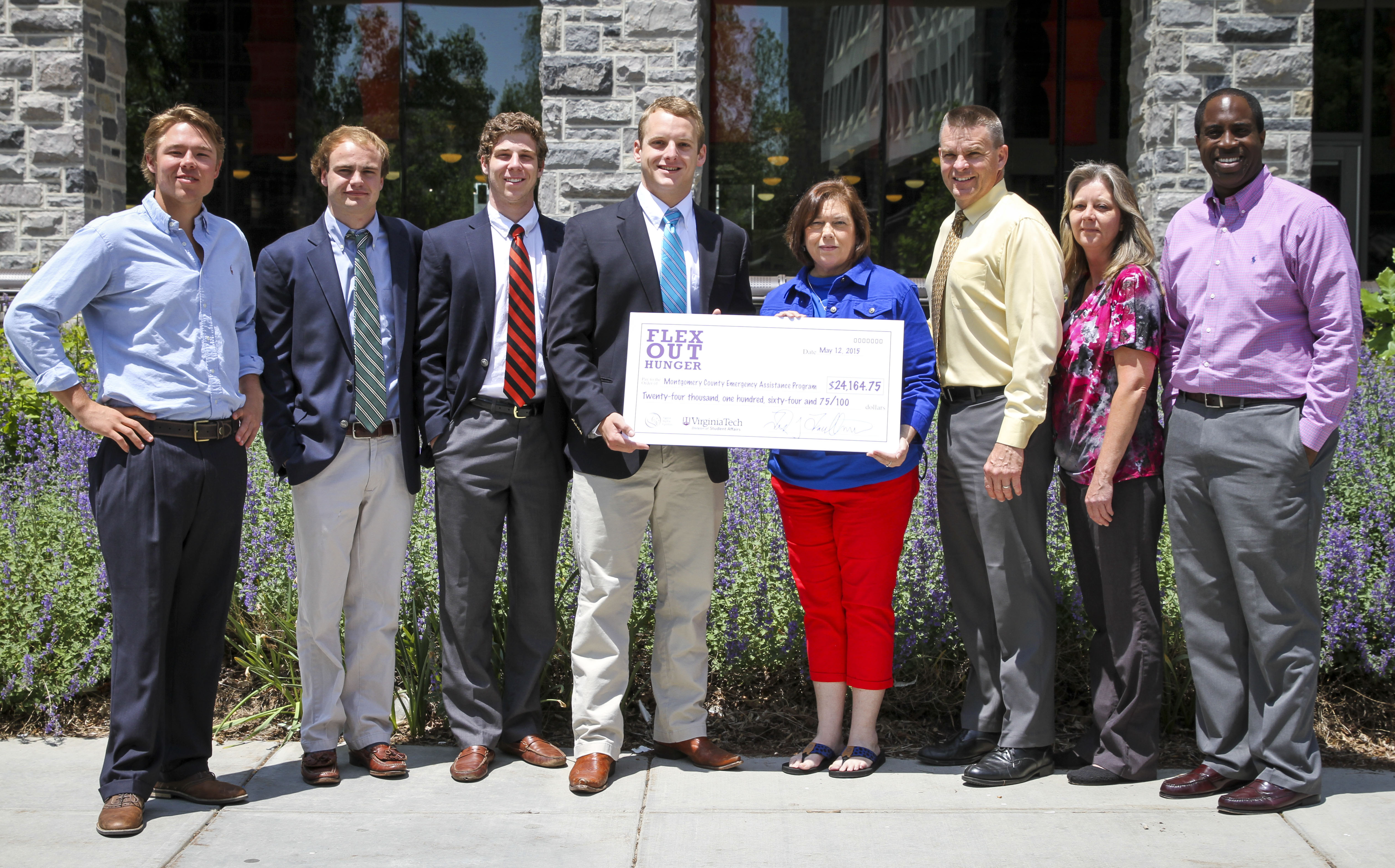 Group image of SAE members and recipients of check.