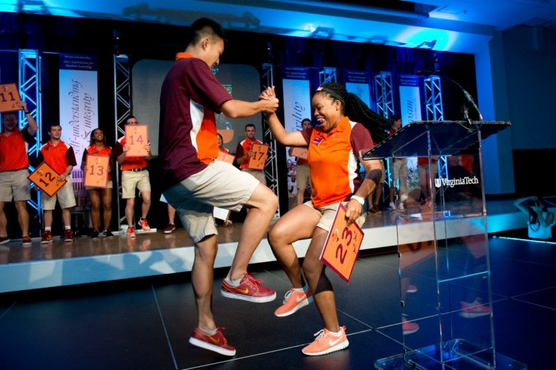 Two Orientation staff members do a handshake on stage at the opening session of Orientation.