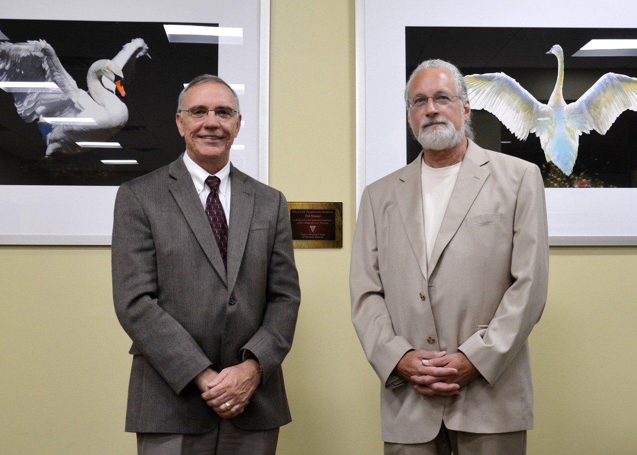 The college recognized Ted Smusz (right), communications assistant, for his art donations with a plaque in the library and student lounge space. Also pictured is Dean Cyril Clarke.