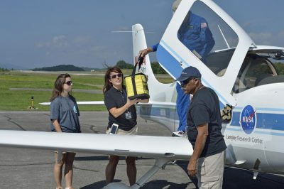 Personnel from Health Wagon and the Appalachian College of Pharmacy receive medical supplies delivered by a NASA SR-22 aircraft.