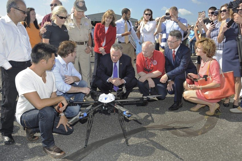 Gov. Terry McAuliffe (third from left) and Virginia Tech President Timothy D. Sands (fifth from left) inspect a Flirtey hexacopter before its flight carrying medicines from the Lonesome Pine Airport to the Wise County Fairgrounds on Friday, July 17, 2015. Researchers were investigating the potential of unmanned aircraft for the delivery of pharmaceuticals and medical supplies in rural areas. Flirtey co-founders (from left) Tom Bass and Matt Sweeney, McAuliffe, Wise County Clerk of Circuit Court Jack  Kennedy, Sands, and Virginia  Secretary of Technology Karen Jackson witnessed the groundbreaking flights.